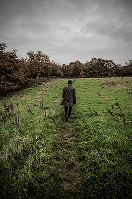 Man in a raincoat and hat walking through a meadow - p1047m987404 by Sally Mundy