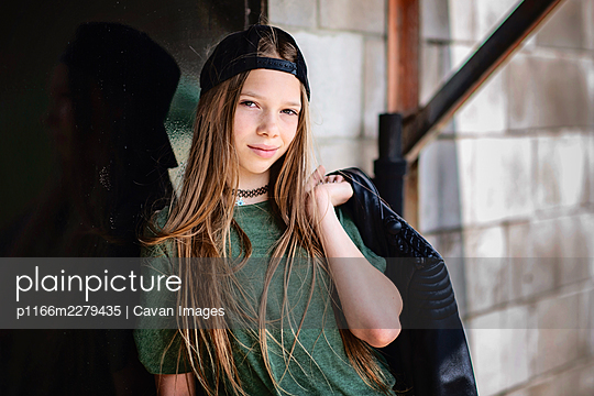 Tween girl with blond hair and black jacket hanging out in the city. - p1166m2279435 by Cavan Images