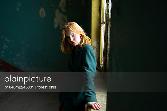 Sad teenage girl with red hair in the staircase - p1646m2245081 by Slava Chistyakov