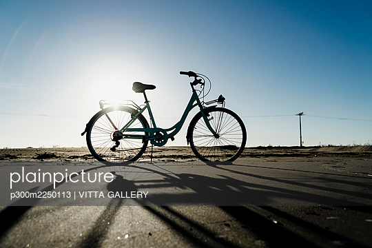 Silhouette bicycle parked at Fangar Beach against clear sky in sunlight, Ebro delta. Spain - p300m2250113 by VITTA GALLERY