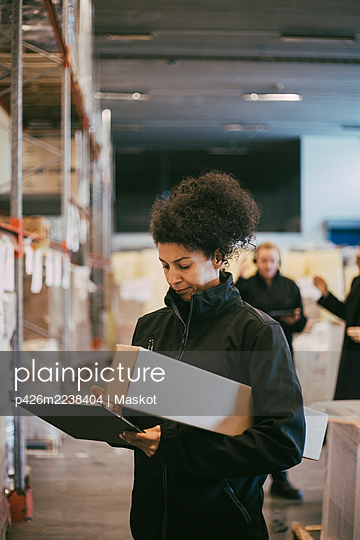 Businesswoman examining while writing on clipboard at distribution warehouse - p426m2238404 by Maskot