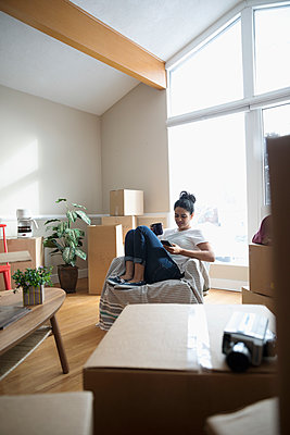 Young woman with smart phone relaxing, taking break from moving house - p1192m1559949 by Hero Images