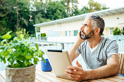 Pensive man with digital tablet sitting on his balcony - p300m965270f by Martin Benik