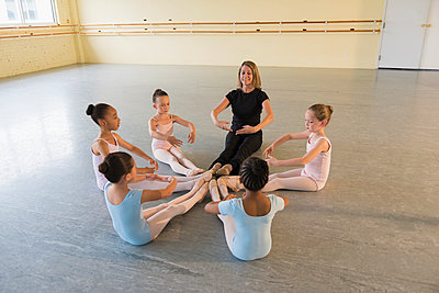 Teacher and students sitting on floor in ballet studio - p555m1491093 by Mark Edward Atkinson