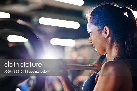 Woman lifting barbell in gym - p300m1581349 von gpointstudio