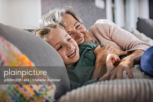 Happy grandmother and granddaughter resting on sofa in living room - p300m2287424 by Stefanie Aumiller