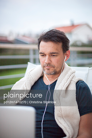 Man with earphones - p312m1470270 by Christina Strehlow