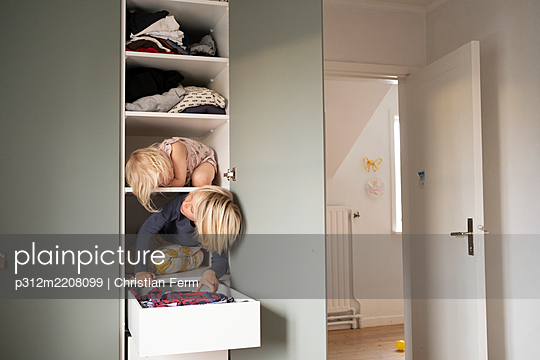 Sisters sitting on shelves in wardrobe - p312m2208099 by Christian Ferm