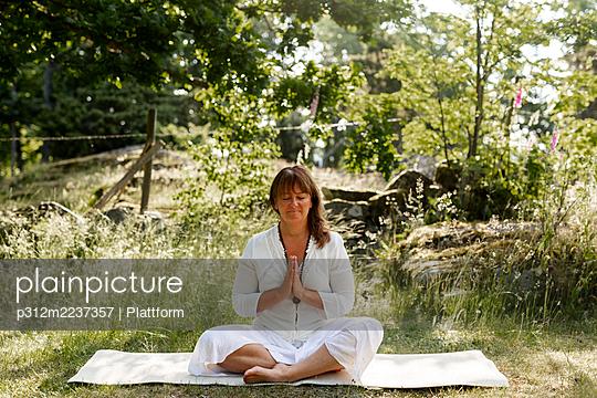 Woman meditating outdoor - p312m2237357 by Plattform