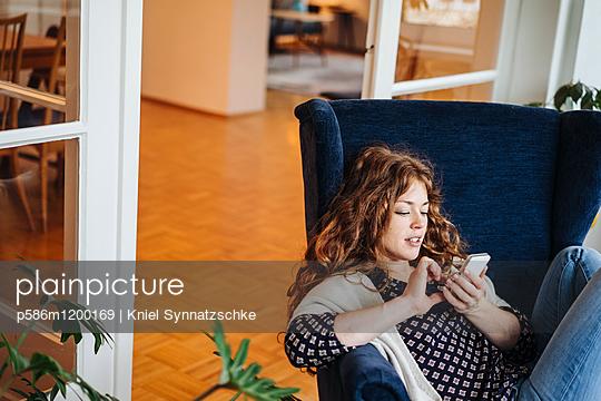 Junge Frau mit roten Haaren schreibt eine SMS - p586m1200169 von Kniel Synnatzschke