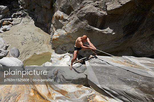 Man uses climbing rope to climb a steep face, Switzerland - p763m1525608 by co-o-peration
