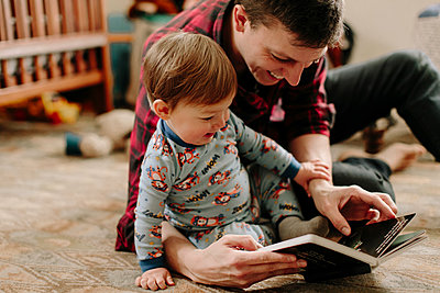 Happy father showing picture book to son while sitting on carpet at home - p1166m1423146 by Cavan Images