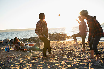 Brother and sisters playing with hacky sack on sunny ocean beach - p1192m1511923 by Hero Images