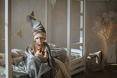 Boy with blanket sitting on the bed  - p1414m1590597 by Dasha Pears