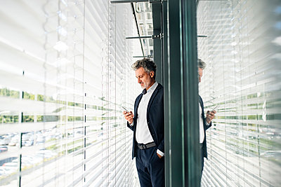 Mature businessman standing at outside sunblind holding cell phone - p300m1536083 by HalfPoint