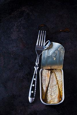 Opened sardine can and fork on dark ground - p300m1587554 by Dieter Heinemann