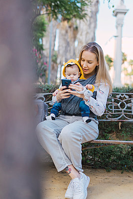 Mother resting with baby boy on a park bench using smartphone - p300m2154834 by Eloisa Ramos