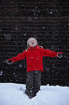 Little girl catching snowflakes - p4294540f by Jakob Helbig