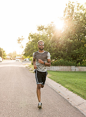 Black man running on street in neighborhood - p555m1522911 by Kolostock