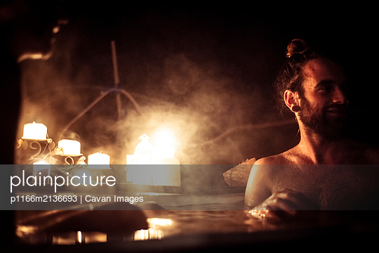 Man with hair in bun sits in out door bath tub in candle light - p1166m2136693 by Cavan Images