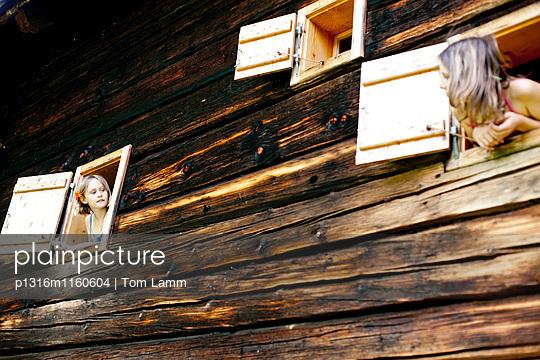 Zwei Mädchen schauen aus einem Bauernhaus, Steiermark, Österreich - p1316m1160604 von Tom Lamm