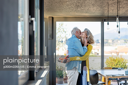 Man embracing woman smiling while holding gift box at home - p300m2265105 by Emma Innocenti