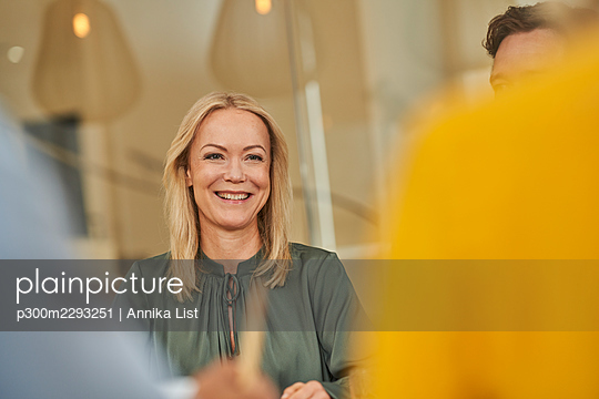 Smiling female professional with colleagues in meeting - p300m2293251 by Annika List