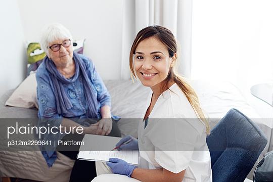 Nurse with elderly woman at home - p312m2299641 by Plattform