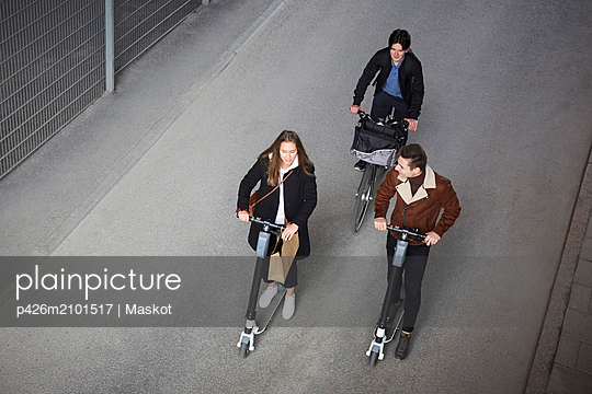 High angle view of teenage friends riding electric push scooters and bicycle on street in city - p426m2101517 by Maskot