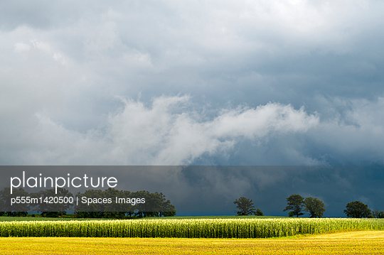 plainpicture | Photo library for authentic images - plainpicture p555m1420500 - Storm clouds over rural lan... - plainpicture/Blend Images/Spaces Images