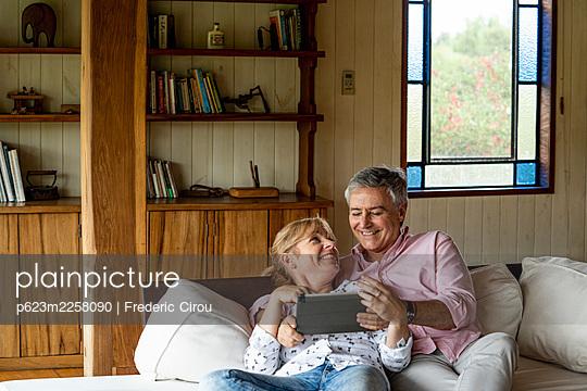 Senior couple using digital tablet - p623m2258090 by Frederic Cirou