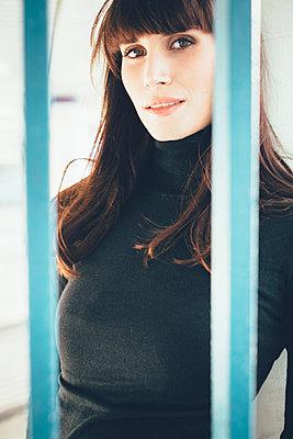 Woman gazing between struts - p1076m926047 by TOBSN