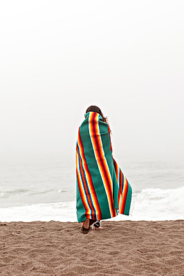 Rear view of woman wrapped in towel walking on shore at beach - p1166m1210778 by Cavan Images