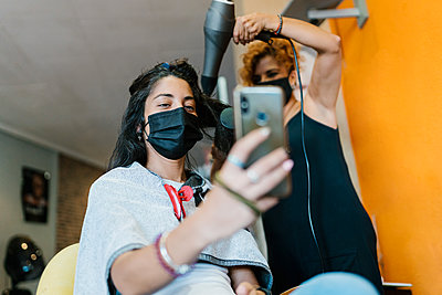 Woman in the hairdresser's with mask, cutting her hair, beauty salon - p1166m2218211 by Cavan Images