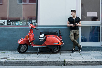 Young man and his red scooter - p1437m1585639 by Achim Bunz