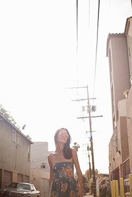 Young woman (23-30) walking down the street, Los Angeles, California, USA - p300m2264516 von LOUIS CHRISTIAN