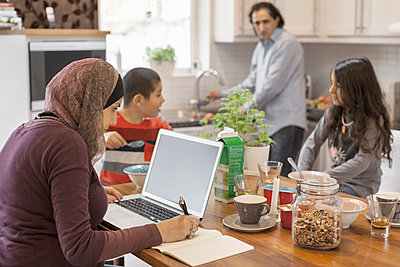Muslim woman working on laptop with family having breakfast in kitchen - p426m896705f by Maskot