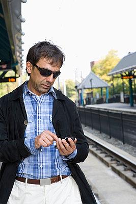 Hispanic man text messaging on train station platform - p555m1419105 by REB Images