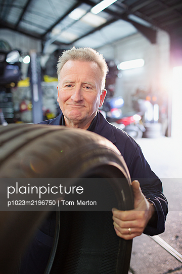 Male mechanic holding tire in auto repair shop - p1023m2196750 by Tom Merton