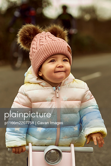 A 1 year old baby girl is with a pink motorcycle outside - p1166m2207758 by Cavan Images