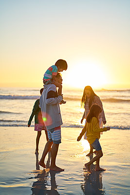 Family wading in ocean surf on sunny beach at sunset - p1023m2200847 by Trevor Adeline