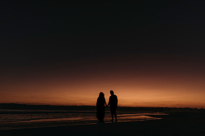 Silhouette of husband and wife walking on beach at sunset - p1166m2136531 by Cavan Images