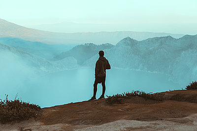 Young man looking at Ijen lake - p1166m2137434 by Cavan Images