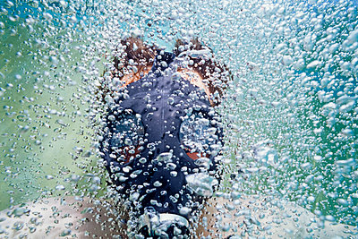 Man underwater with a gas mask and bubbles. - p1166m2162794 by Cavan Images