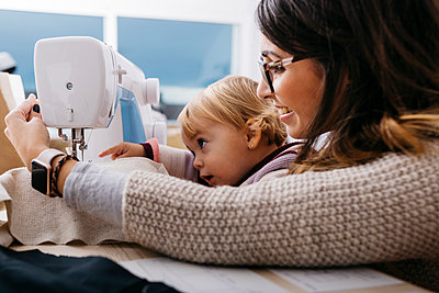 Happy mother with little daughter at home using sewing machine - p300m2058997 by Josep Rovirosa