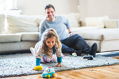 Happy man looking at daughter playing with toys at home - p426m2127440 by Maskot