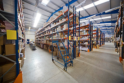 Shelving in a warehouse - p4428513f by Design Pics