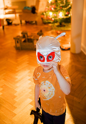 Boy wearing mask on christmas eve - p528m718565f by Susanne Kronholm