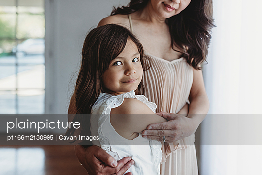 Mid level view of school aged girl being hugged by mother - p1166m2130995 by Cavan Images