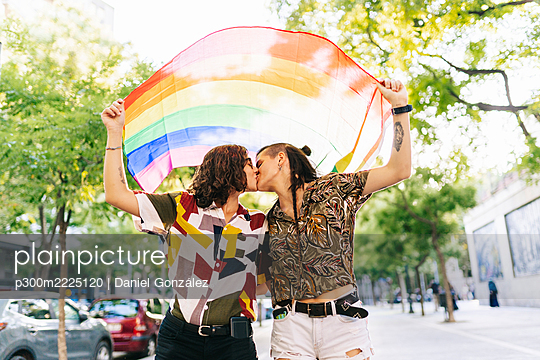 Lesbian couple holding rainbow flag while kissing on footpath in city - p300m2225120 by Daniel González